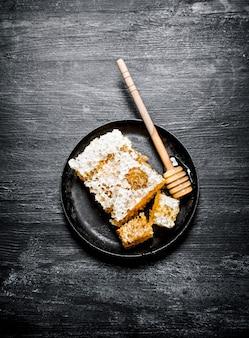 Miele aromatizzato dolce nel pettine con un cucchiaio nella padella. su sfondo nero rustico.
