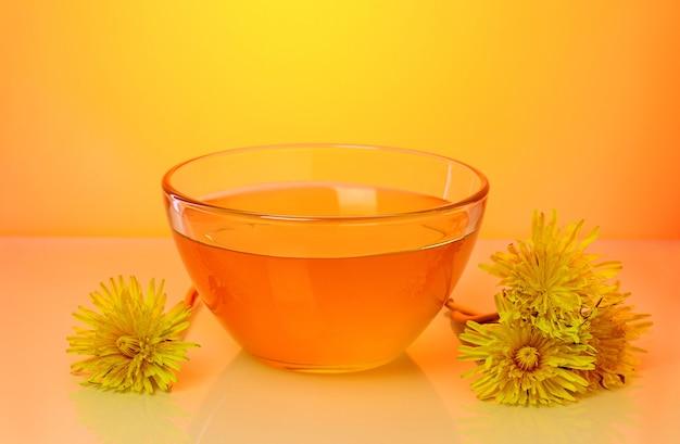 Dolce miele floreale in una ciotola di vetro e fiori di tarassaco vicino, su sfondo arancione brillante.