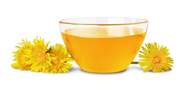 Dolce miele floreale in ciotola di vetro e fiori di tarassaco vicino, isolato su sfondo bianco.