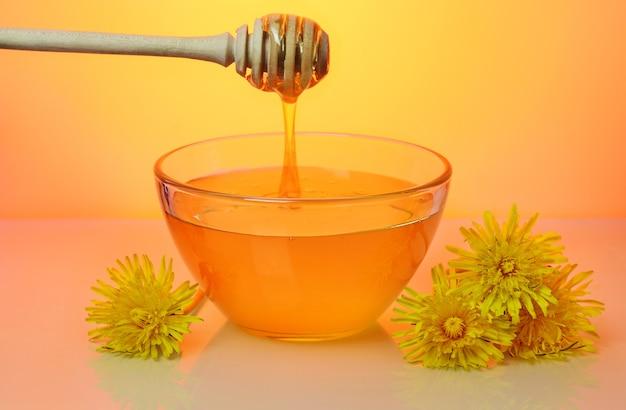 Dolce miele floreale che versa da drizzler in lastra di vetro e fiori di tarassaco vicino, su sfondo arancione brillante.