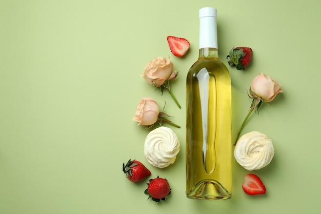 Cibo dolce e bottiglia di vino vuota su sfondo verde