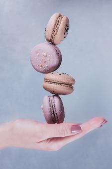 Biscotti dolci francesi dei macarons impilati sulla mano della donna contro la superficie grigia. pastello colorato amaretti volanti. concetto di cibo, cucina e cucina