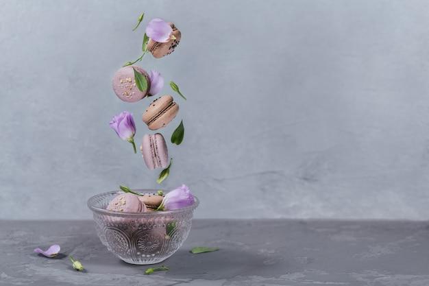 Dolci macarons francesi cadono mescolati con fiori in una ciotola. pastello colorato amaretti volanti biscotti. superficie grigia. concetto di cibo, cucina, al forno e cucina