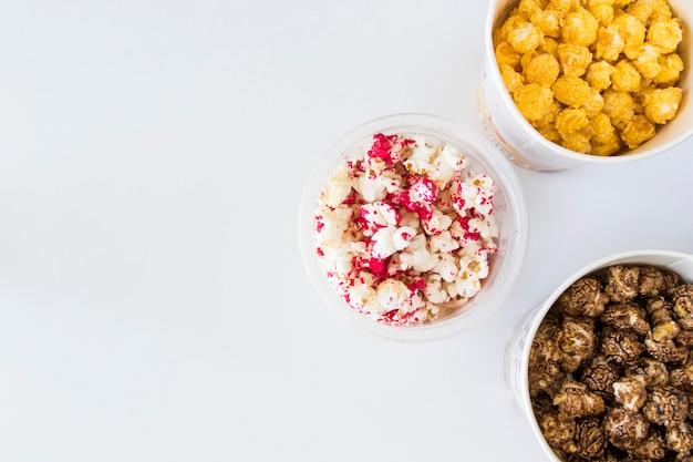 Popcorn fritto dolce in ciotola sui precedenti bianchi