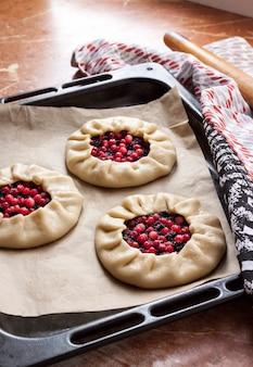 Galetts dolci con bacche di sambuco e mirtilli rossi sulla teglia pronta per la cottura