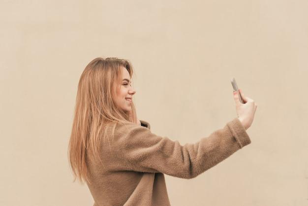 Dolce ragazza in un elegante abito di primavera, indossa un cappotto, in piedi sullo sfondo di una parete beige e prende selfie su uno smartphone