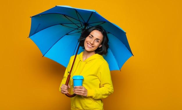 Dolce ragazza con un ampio sorriso sul viso sotto un ombrello, vestita con una felpa con cappuccio gialla, con una tazza termica blu nella mano sinistra.