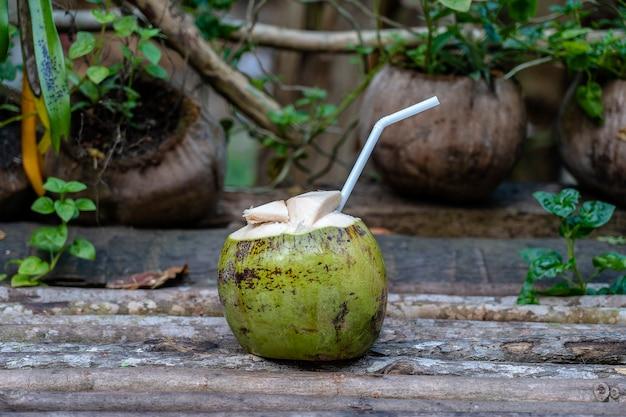 Acqua di cocco verde dolce con cannuccia su tavola di legno. frutta tropicale della noce di cocco nell'isola koh phangan in thailandia. avvicinamento