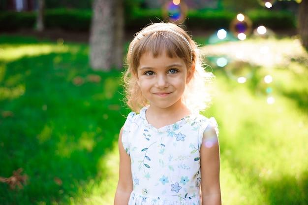 Dolce, felice, sorridente bambina di cinque anni con eterocromia due occhi colorati posa su un prato in un parco giocando con le bolle e ridendo