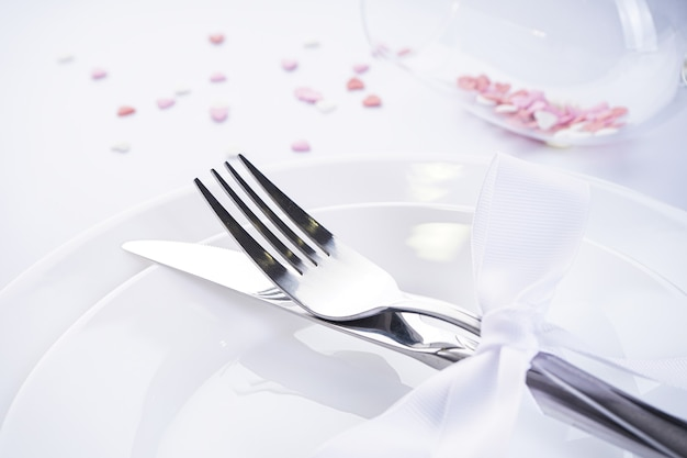 Cuori dolci in un bicchiere con posate e un nastro bianco su sfondo bianco. san valentino. concetto di amore. con posto per il testo.