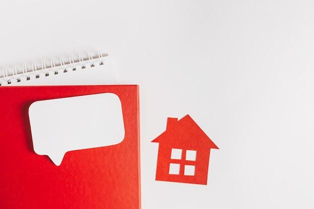 Dolce casa. stima e pagamento dell'imposta sulla casa. mock up con casa rossa, blocco note e adesivo bianco