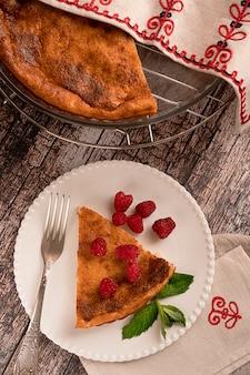 Torta di formaggio fatta in casa dolce servita con lamponi su un piatto bianco