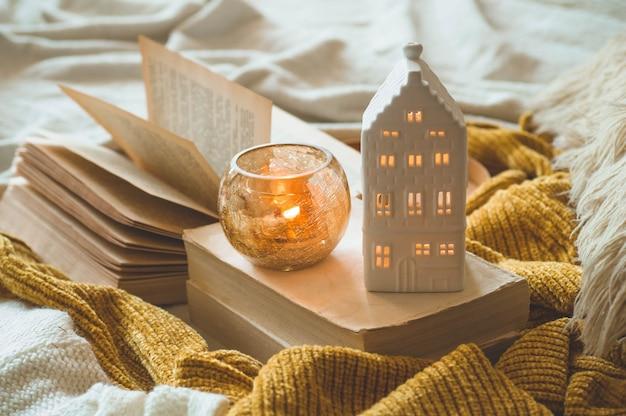 Dolce casa. dettagli di natura morta all'interno della casa del soggiorno. maglioni e candele, decorazioni autunnali sui libri. leggi, riposa. accogliente autunno o inverno concetto.