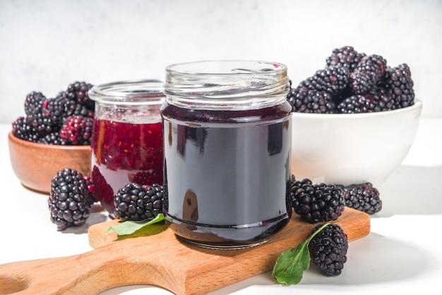 Confettura di more fatta in casa dolce in un piccolo barattolo di vetro su sfondo bianco, con spazio per la copia di bacche fresche