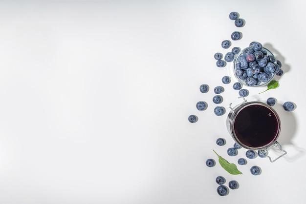 Confettura di mirtilli fatta in casa dolce in un piccolo barattolo di vetro su sfondo bianco, con spazio per la copia di bacche fresche