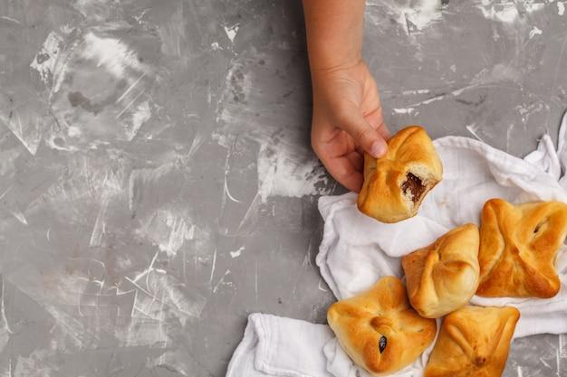 Panini dolci fatti in casa con marmellata di frutta e latte in un bicchiere, sfondo grigio.