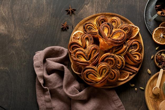 Dolci panini alla cannella fatti in casa a forma di cuore su un vecchio stile retrò. umore del nuovo anno.