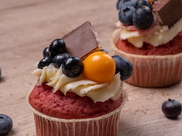 Cupcakes dolci fatti in casa con mirtilli e mousse di panna. circondato da mirtilli. cucinare prodotti da forno a casa.