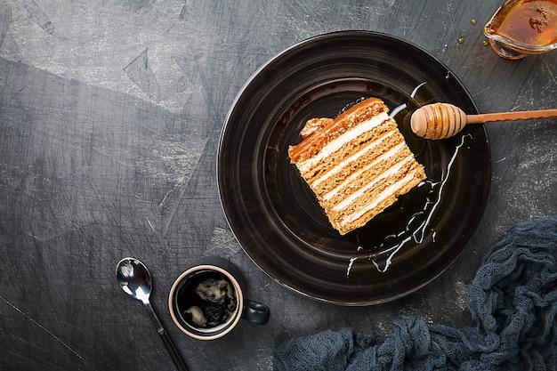 Torta di miele stratificata fatta in casa dolce su una superficie nera, vista dall'alto