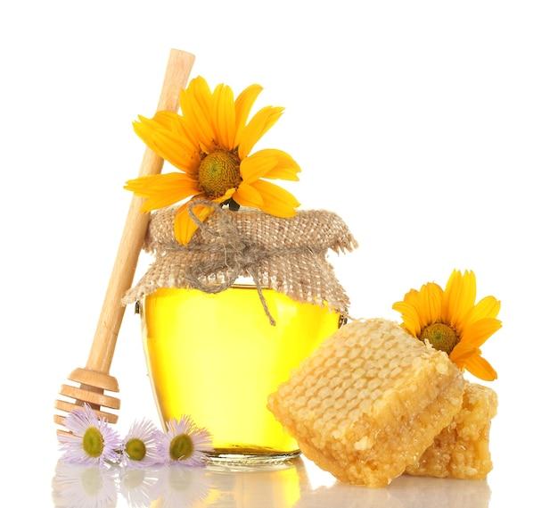 Dolce miele in vaso con nido d'ape, drizzler in legno e fiori isolati su bianco