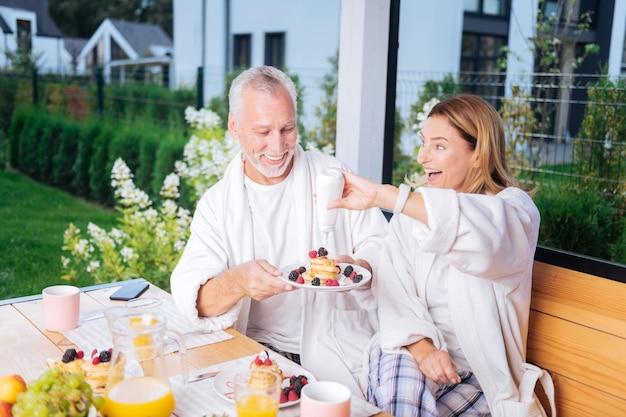 Dolcezza. moglie sorridente che mette un po 'di miele dolce sulle frittelle del marito raggiante mentre fanno colazione insieme