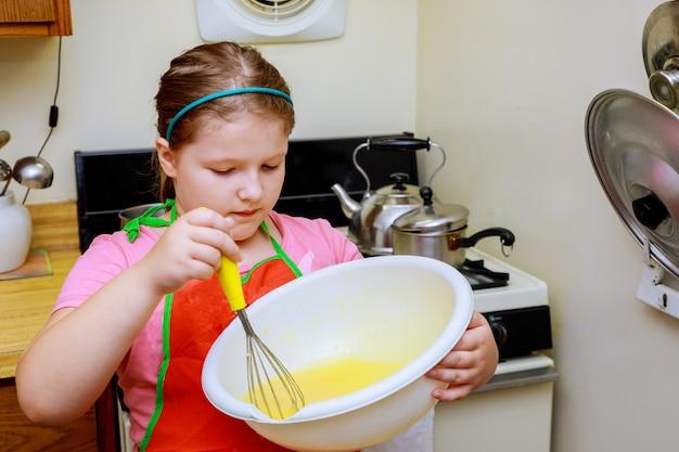 Una dolce ragazzina carina sta imparando a fare una torta, in cucina a casa