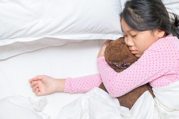 Dolce bambina sta abbracciando un orsacchiotto mentre dorme nel suo letto a casa, riposo e concetto di assistenza sanitaria