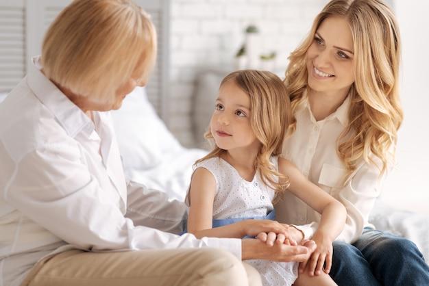 Dolce bambina seduta nell'abbraccio della sua affascinante madre bionda e guarda attentamente la nonna che le dice qualcosa