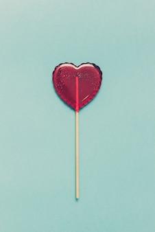 Lecca-lecca dolce su sfondo blu. cuore rosso. caramella. concetto di amore. giorno di san valentino