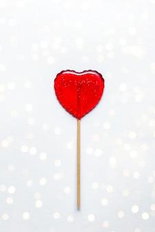 Lecca-lecca dolce su sfondo bianco con bokeh. cuore rosso. caramella. concetto di amore. giorno di san valentino