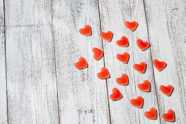 Forma di cuore della caramella rossa della marmellata d'arance dolce sulla tavola di legno bianca, composizione nel giorno di san valentino con copyspace.