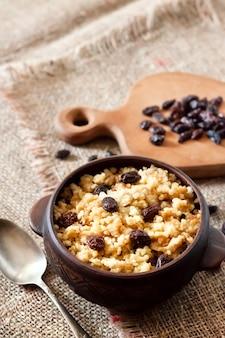 Porridge di miglio dolce con uvetta scura in ciotola rustica in ceramica con noci sullo sfondo. copia spazio