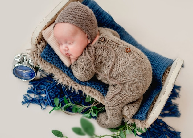 Dolce neonato che dorme nel lettino con indosso un abito lavorato a maglia e un cappello. bellissimo ritratto di un neonato