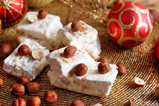 Torrone dolce con nocciole e tavola di decorazione natalizia si chiuda