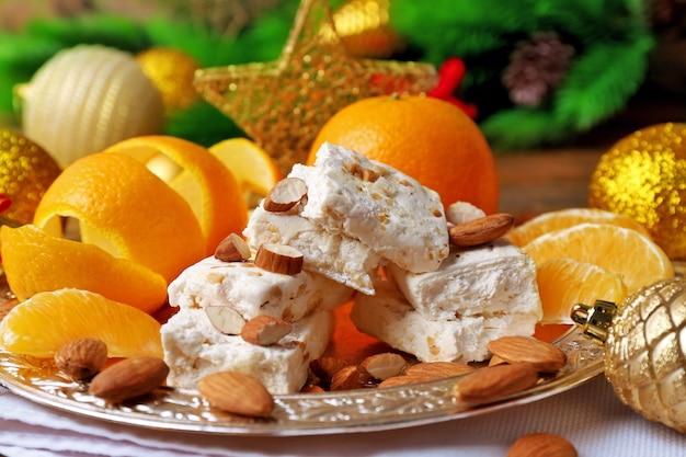 Torrone dolce con arance e decorazioni natalizie sul tavolo da vicino