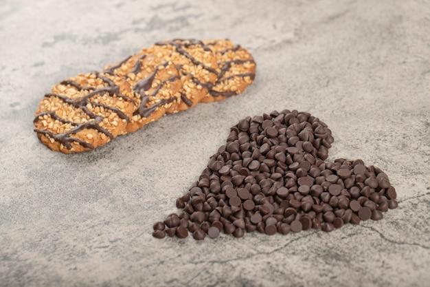 Biscotti di farina d'avena dolce e cioccolato a goccia posto sul tavolo di pietra.