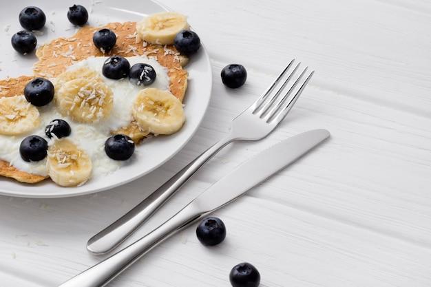 Frittelle di farina d'avena dolci con crema, mirtillo e banana. concetto di colazione sana.