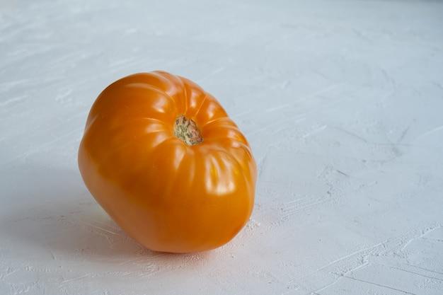 Pomodoro di ciliegia arancio dolce su fondo bianco.