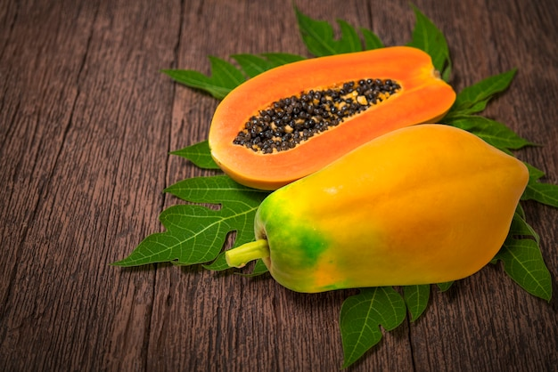 Papaia dolce sul piatto con foglia di papaia verde su fondo in legno.