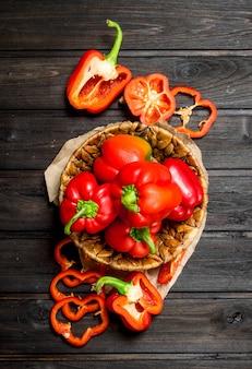 Peperone dolce in un cesto e pezzi di pepe fresco. sullo sfondo di legno