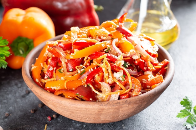 Peperoni con carote coreane, semi di sesamo e verdure in una ciotola su uno sfondo scuro. cibo sano piccante