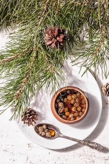 Confettura di pigne dolce. dolce tradizionale siberiano, rami sempreverdi freschi. luce dura alla moda, ombra scura. fondo in legno bianco, vista dall'alto
