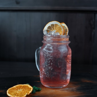 Dolce cocktail alcolico rosa con martini con vodka con sciroppo di fragole decorato con fette d'arancia essiccate si trova su un tavolo di legno in un caffè. cocktail d'autore nel bicchiere originale.