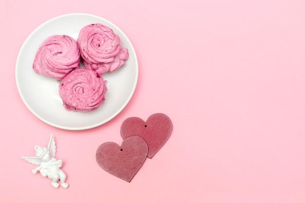 Dolce marshmallow rosa sul piatto, decorazioni di angelo a forma di cuore e cupido, concetto di san valentino con spazio copia su sfondo rosa.