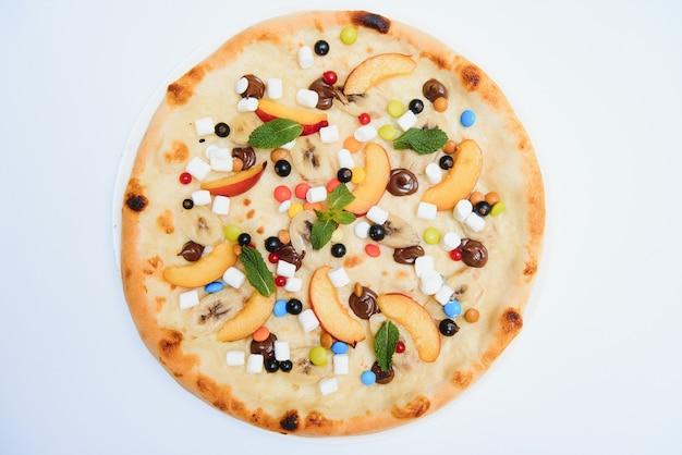 Pizza dolce con salsa marshmallow e caramelle colorate, pizza al cioccolato con caramelle colorate e pizza al cioccolato con banana su sfondo bianco