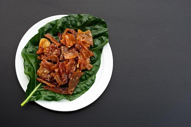 Maiale dolce o carne di maiale essiccata su superficie scura. vista dall'alto