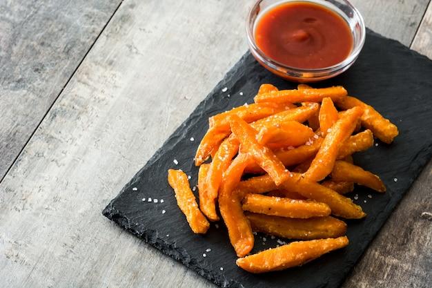 Patate fritte e salsa ketchup sulla tavola di legno