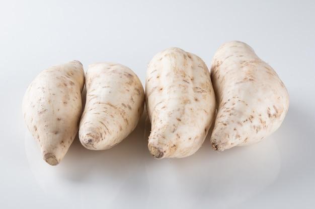 Patata dolce isolata su superficie bianca.