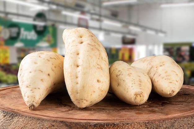 Patata dolce su legno su superficie vaga.