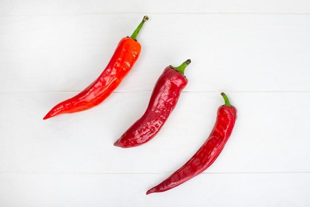 Kapi dolce del peperone, tre peperoni sulla tavola di legno bianca